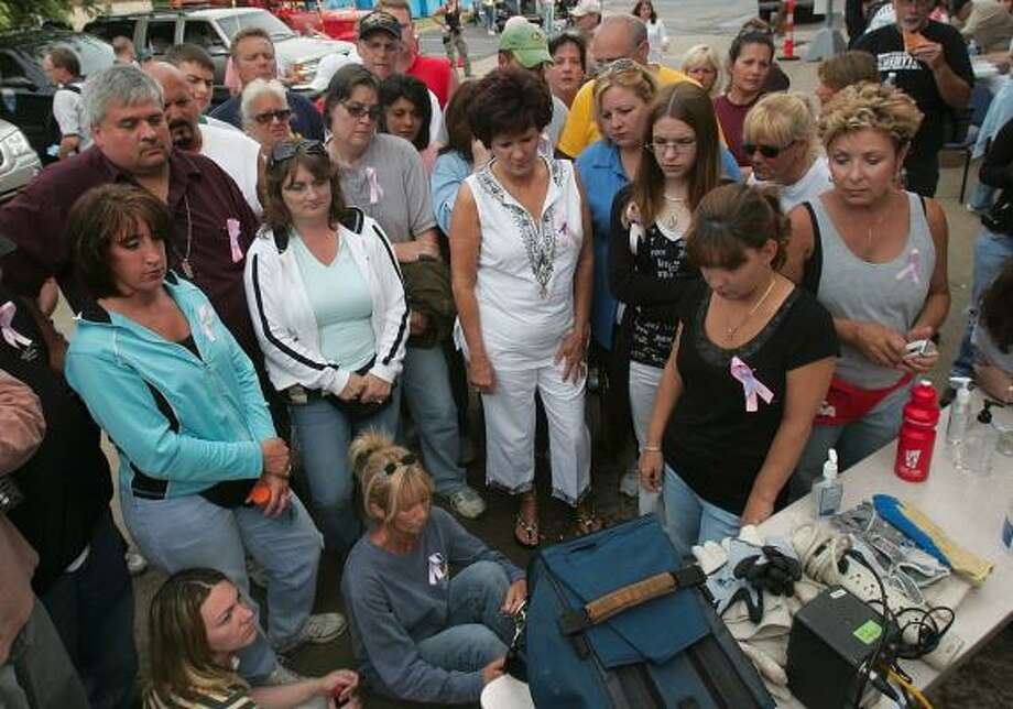 Volunteers watch a televised news conference Saturday after the discovery of a body thought to be that of Jessie Marie Davis, 26, who was nine months pregnant and had been missing a week. Photo: PHIL MASTURZO, AKRON BEACON JOURNAL