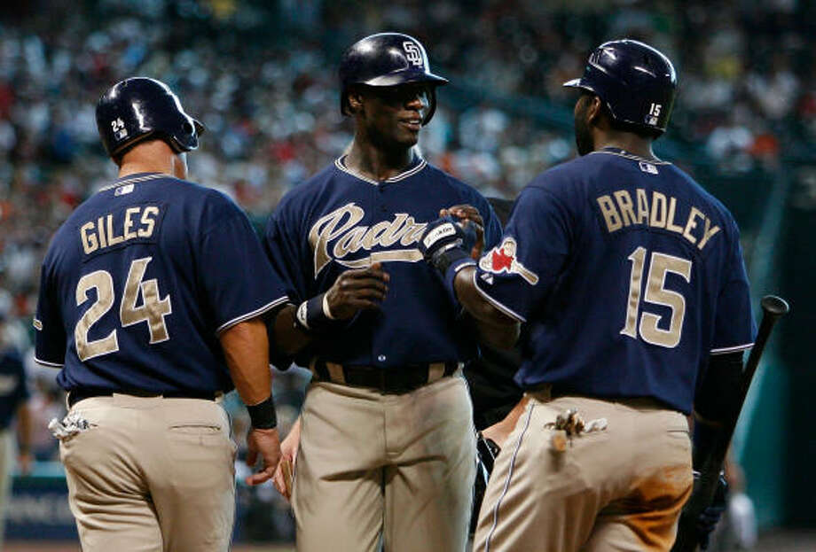 San Diego Padres Mike Cameron, center, is congratulated after his two-run home run that scored Brian Giles, left, as Milton Bradley waits for his at bat in the top of the first inning. Photo: Kevin Fujii, Chronicle