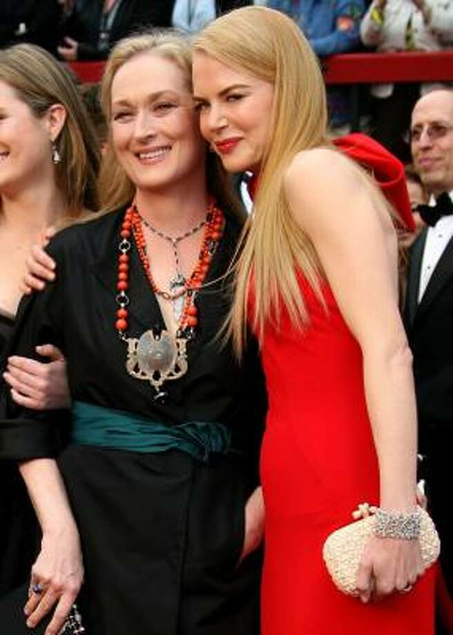 Meryl Streep, in a nod to the film that brought her to the Oscars, wore a Prada black silk radzmire coat. Nicole Kidman's bright red Balenciaga halter gown featured an oversized bow. Photo: FRAZER HARRISON, GETTY IMAGES