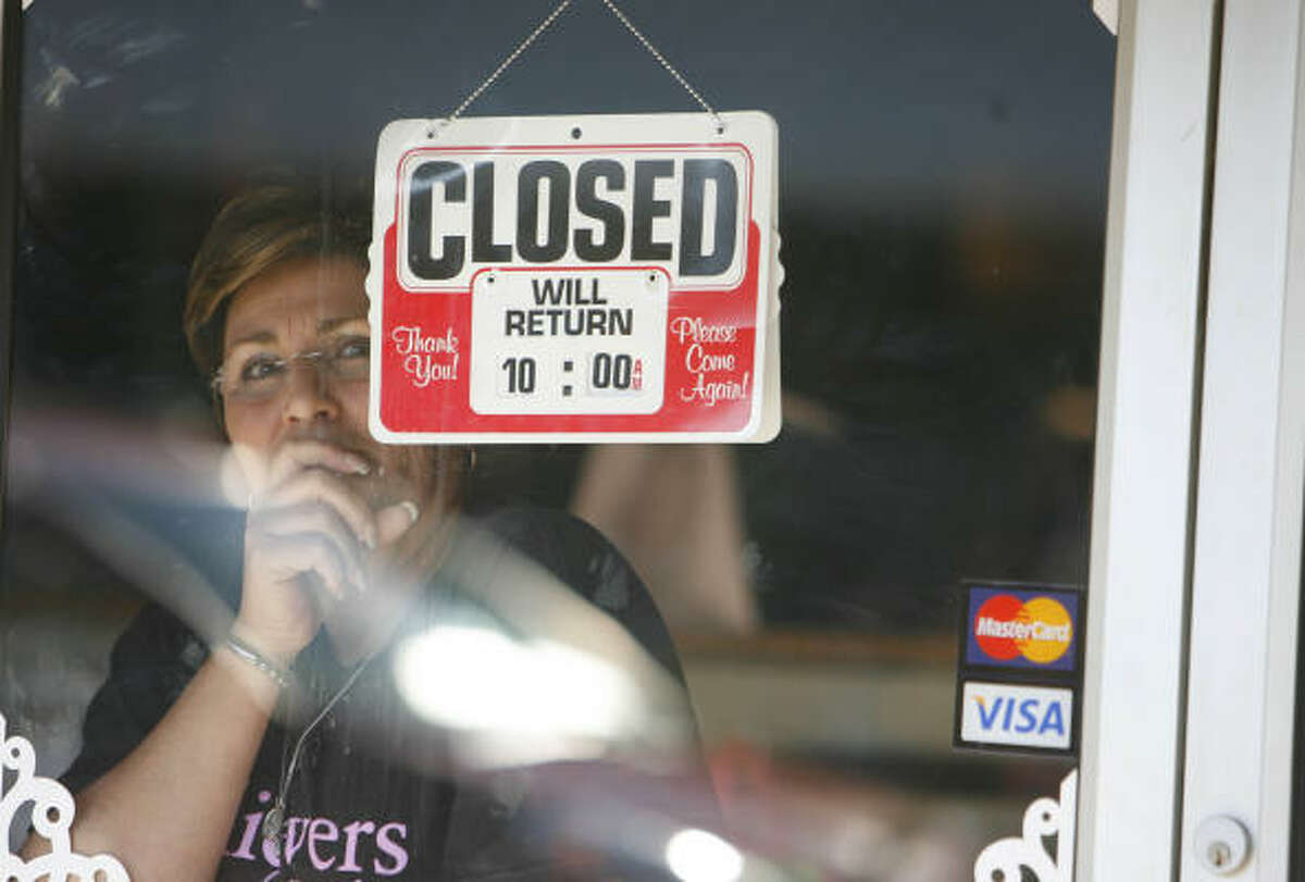 A woman watches from inside a downtown Jena shop as thousands participate in the protest.