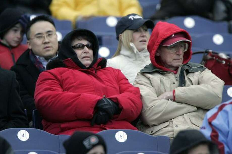 Bundled fans in Philadelphia watch the Phillies drop to 0-3, and scattered snowflakes fell during the game. Photo: George Widman, AP