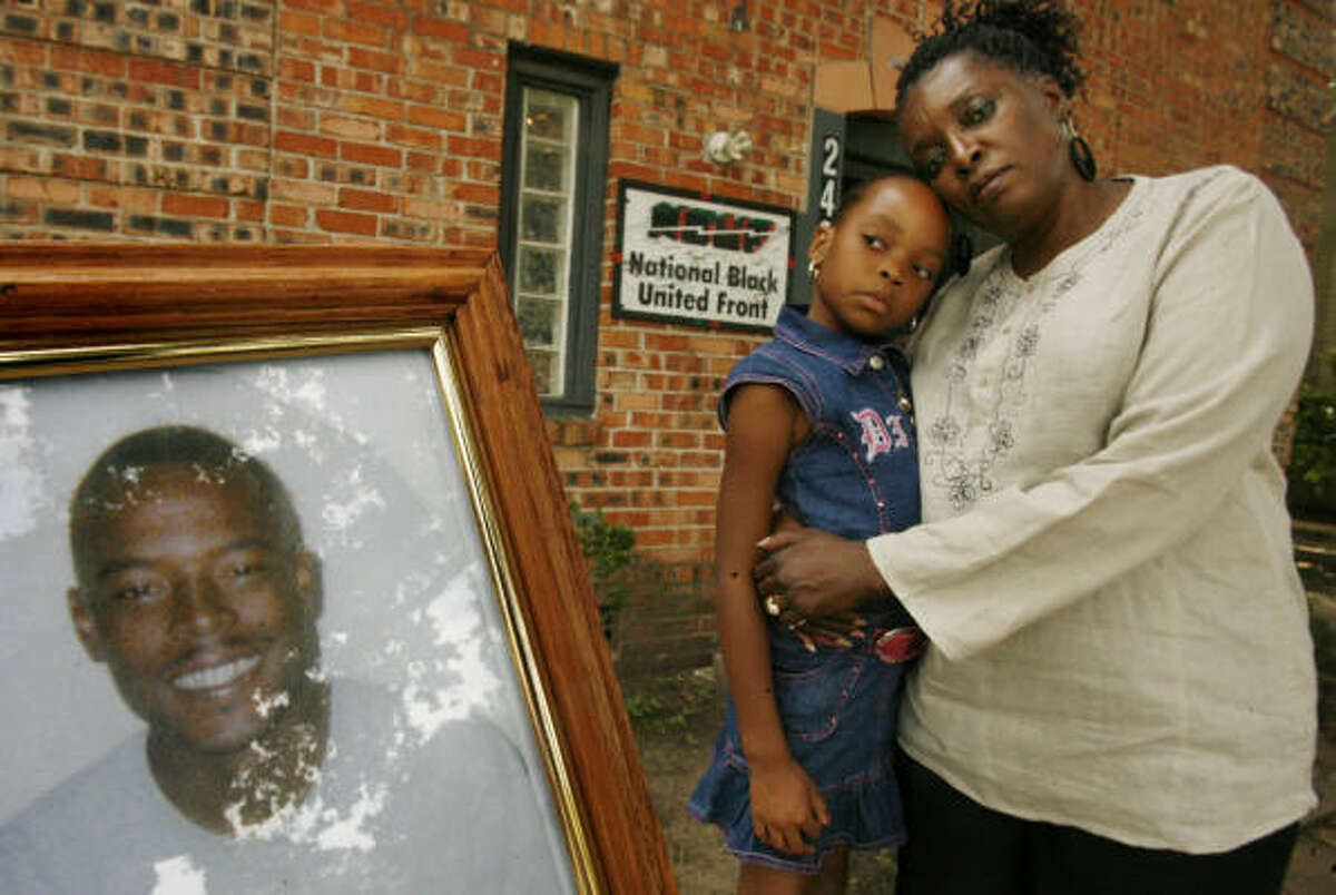 Etta Francis, seen holding her granddaughter Whitney Ann Francis, 8, says she has forgiven Garrett William Mallot in the death of her son and Whitney's father, Otis James Francis, in the picture at left.