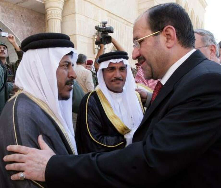 Shiite Iraqi Prime Minister Nouri al-Maliki, right, greets a Sunni tribal leader Friday during a bold visit to Tikrit, hometown of Saddam Hussein. Photo: Handout/Iraqi Prime Minister's Office, AFP/Getty Images