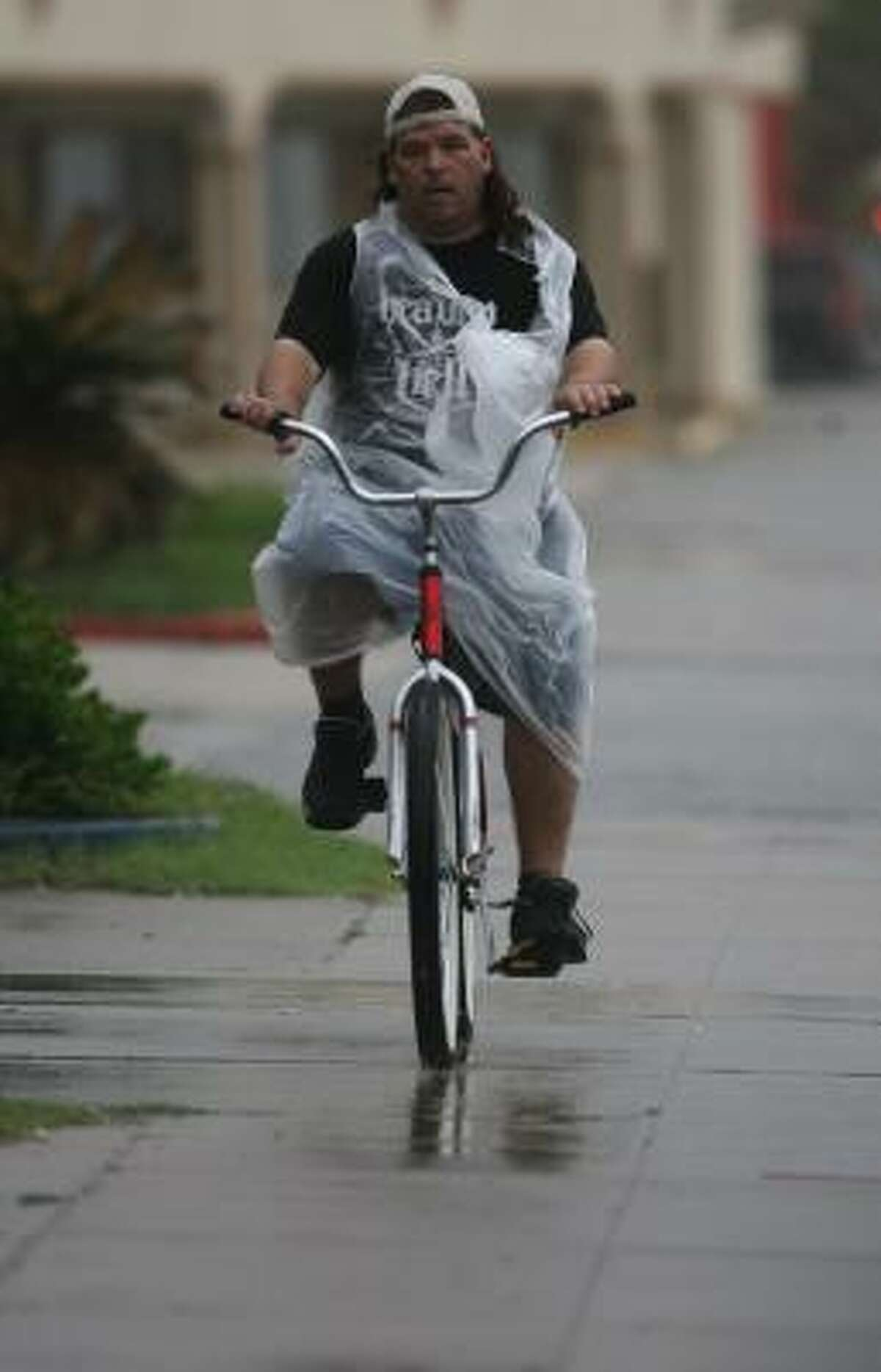 A man bikes down the street in Galveston as Tropical Storm Humberto approaches Wednesday.