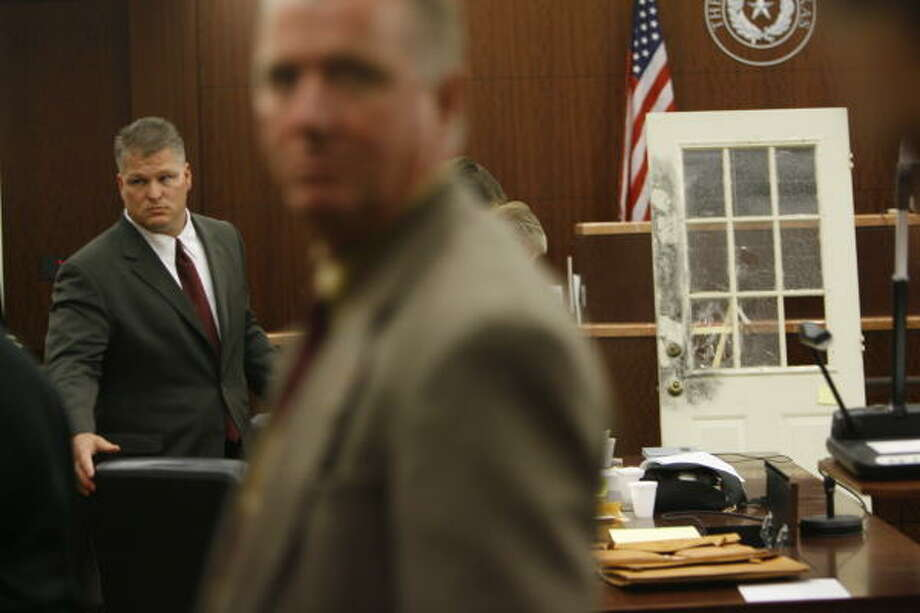 David Temple, background, leaves court Tuesday afternoon after a day that featured opening statements in his trial for the death of his wife, Belinda. The door at right is from the Temples' home in Katy. The defense claims the glass was smashed when the killer broke into the home. Photo: Kevin Fujii, Chronicle