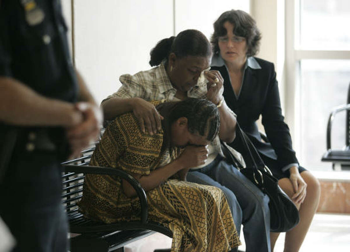 Renee Johnson, left, is comforted by a family friend, Dorothy Brooks, center, and attorney Danalynn Recer after Johnson's son, Dexter Johnson, 19, was sentenced to death in 2007 for the capital murder of Maria Aparece, 23, in the Harris County Criminal Justice Center in Houston.