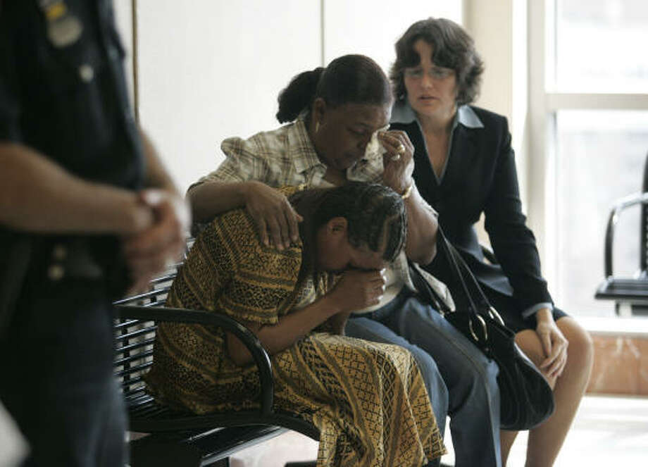 Renee Johnson, left, is comforted by a family friend, Dorothy Brooks, center, and attorney Danalynn Recer after Johnson's son, Dexter Johnson, 19, was sentenced to death Wednesday for the capital murder of Maria Aparece, 23, in the Harris County Criminal Justice Center in Houston. Photo: Johnny Hanson, For The Chronicle