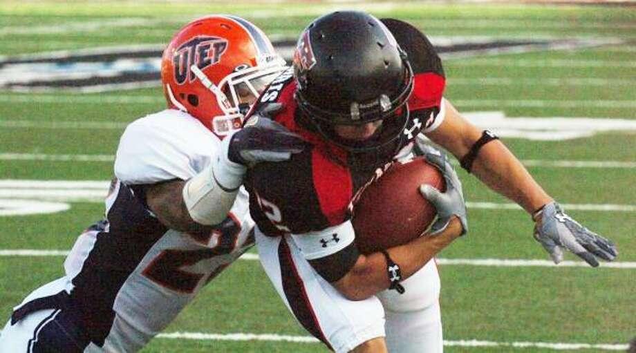 UTEP's Da'Mon Cromartie-Smith (23) drags down Texas Tech receiver Eric Morris. Photo: JOE DON BUCKNER, ASSOCIATED PRESS