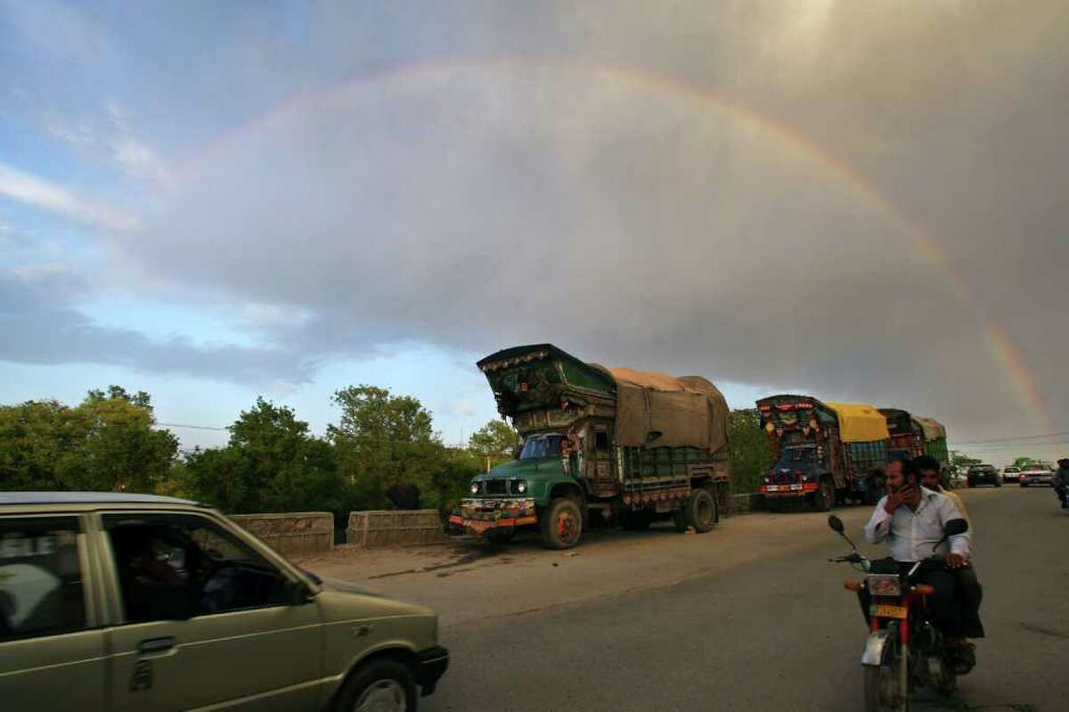 Pakistani commuters cross a street under a rainbow in Islamabad on April 21, 2011.
