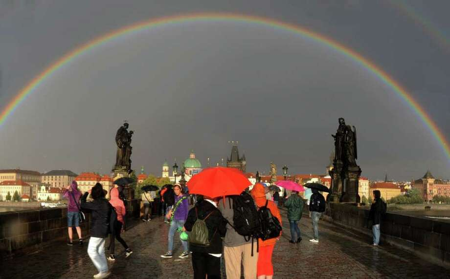 Rainbows are caused by water droplets spreading light into its spectrum of colors. Notice that the sun is alwasy behind you when you face a rainbow, with rain in the direction of the rainbow. Here are some cool rainbows in interesting places around the world, starting with one on August 9, 2011 above the medieval Charles Bridge in Prague, Czech Republic. Photo: MICHAL CIZEK, AFP/Getty Images / 2011 AFP