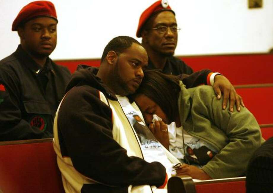 Members of the New Black Panther Party, back, sit as Allen McIntosh Jr. comforts his mother, Danita McIntosh, at a community meeting at The Greater Lighthouse Church on Wednesday. Photo: BILLY SMITH II, CHRONICLE