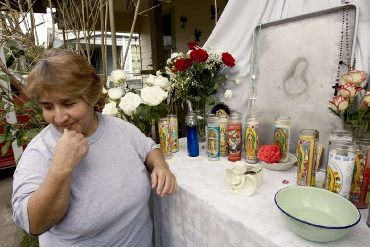 Guadalupe Rodriguez, who discovered the Virgin Mary image, stands next to a makeshift display at a Denver Harbor residence.