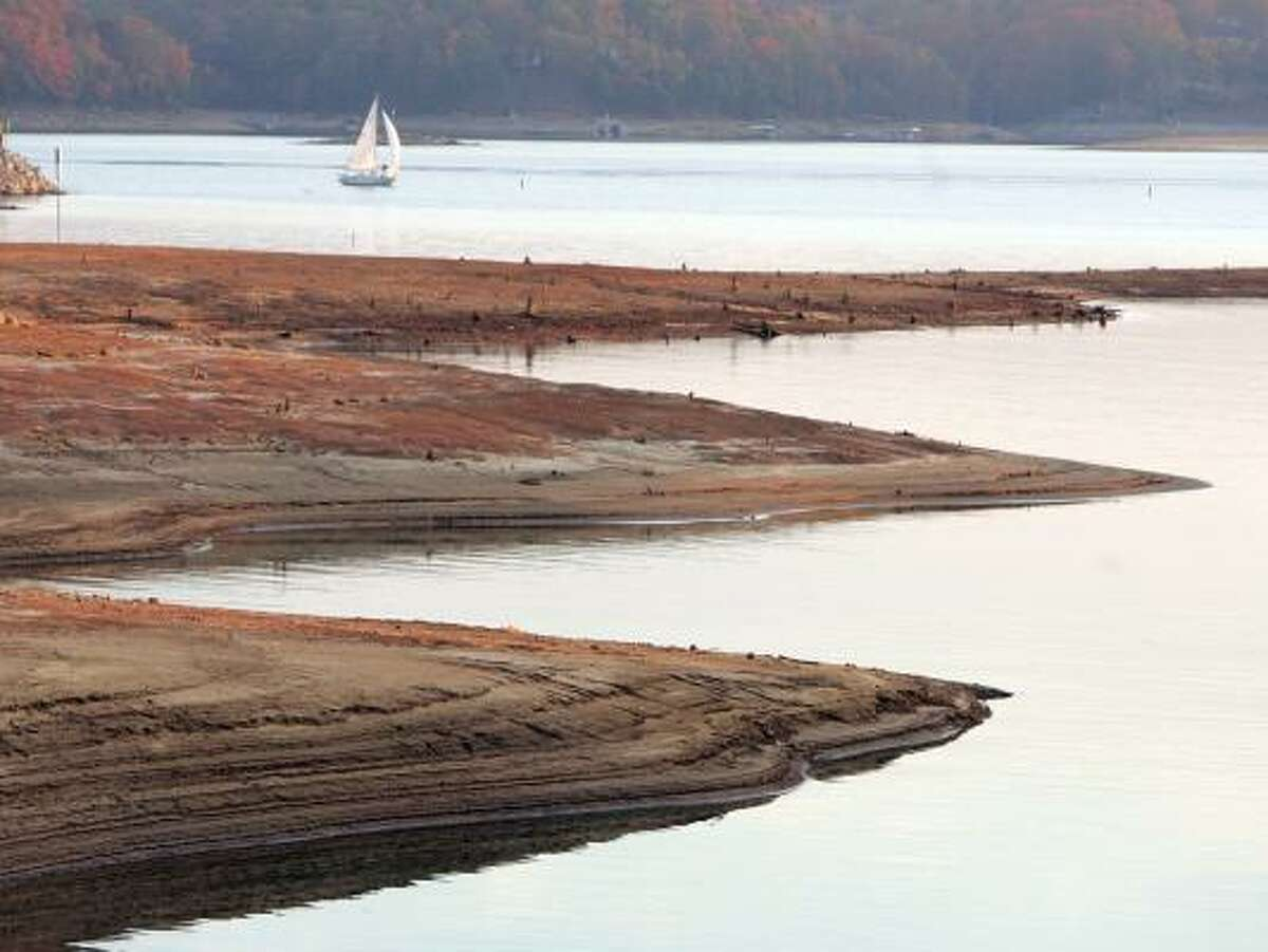 A sailboat glides past the exposed bottom of Lake Lanier in Flowery Branch, Ga. Gov. Sonny Perdue has ordered water restrictions in the Peach State, launched a legal battle and asked for federal help.