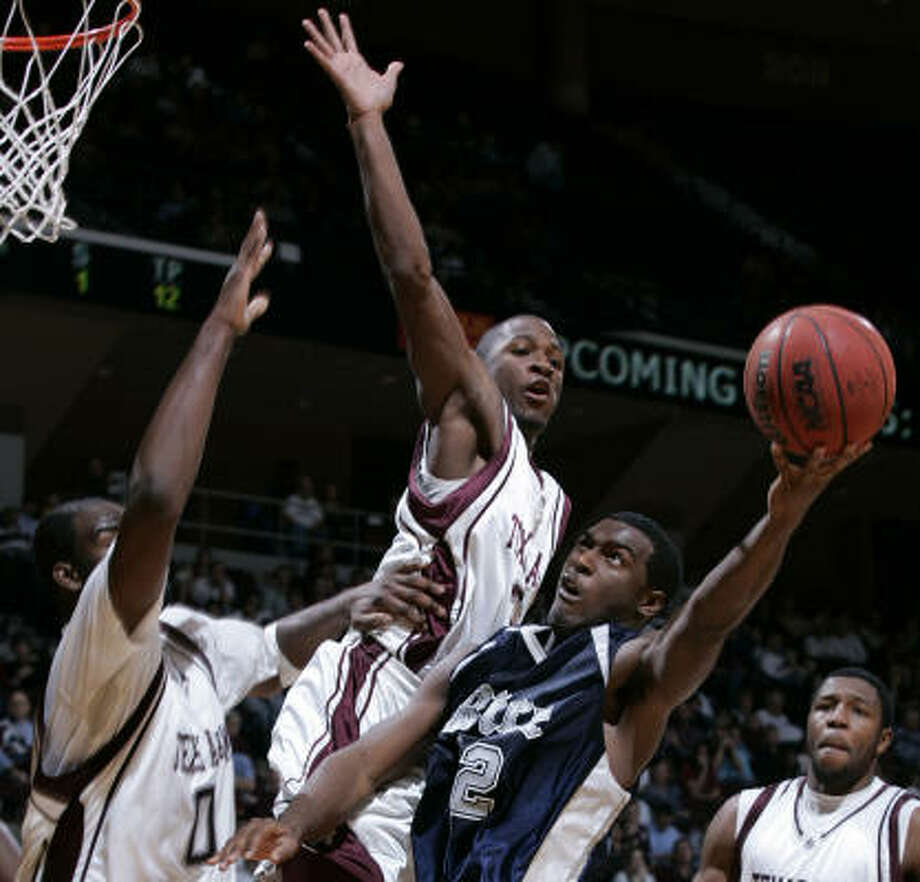 Derrick Roland (middle) tries for a block for the Aggies against Rice's Chinemelu Elonu. Elonu saw 10 minutes of action off the bench. Photo: Paul Zoeller, AP