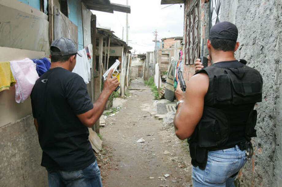 """Members of the """"militia"""" guard the streets in Rio de Janeiro, in January. Militia, new, illegal security forces are mushrooming across Rio and are made up of active and former police, private security guards and off-duty firefighters and prison guards. Photo: Wilton Junior, AP"""