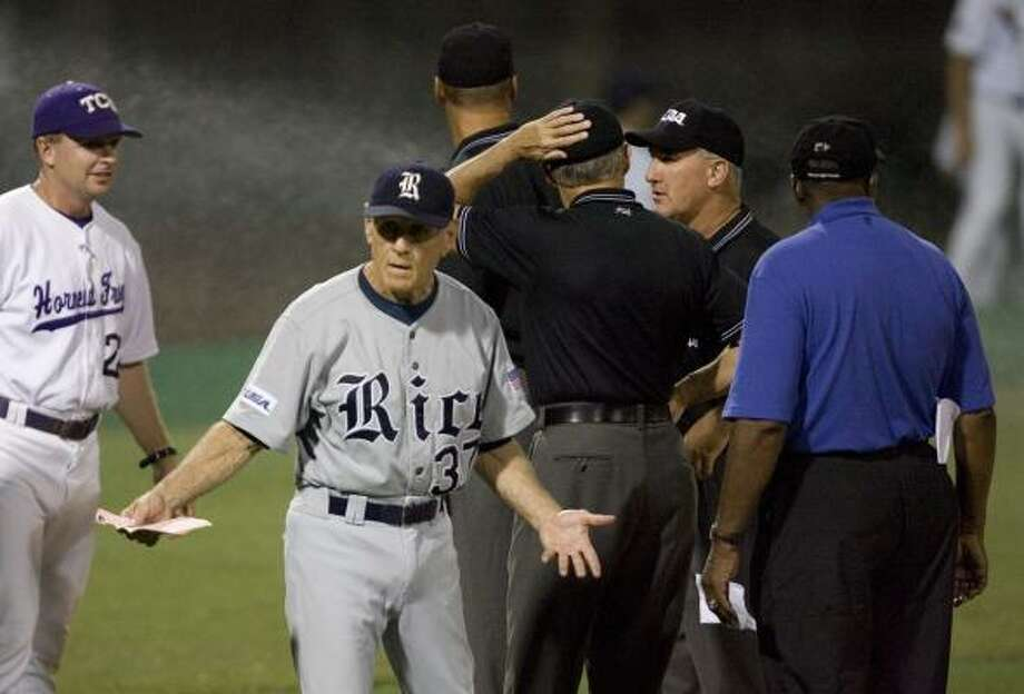 A sprinkler system came on after the rain delay but before the first pitch. Rice's Wayne Graham beckoned to the dugout before the game. Photo: Bob Levey, AP