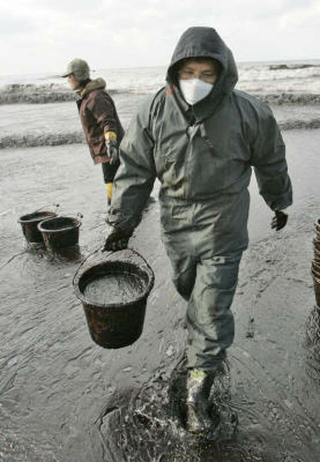 A man carries away a basket full of crude oil removed from Mallipo beach, west of Seoul, South Korea, on Saturday. Photo: Lee Jin-man, Associated Press