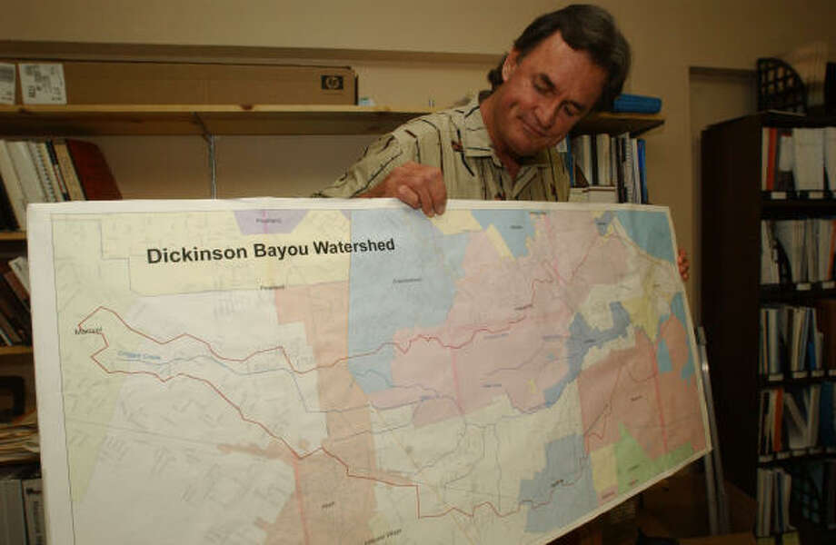 Bud Solmonsson looks at a map of the Texas Coastal Watershed. Photo: Jimmy Loyd, For The Chronicle