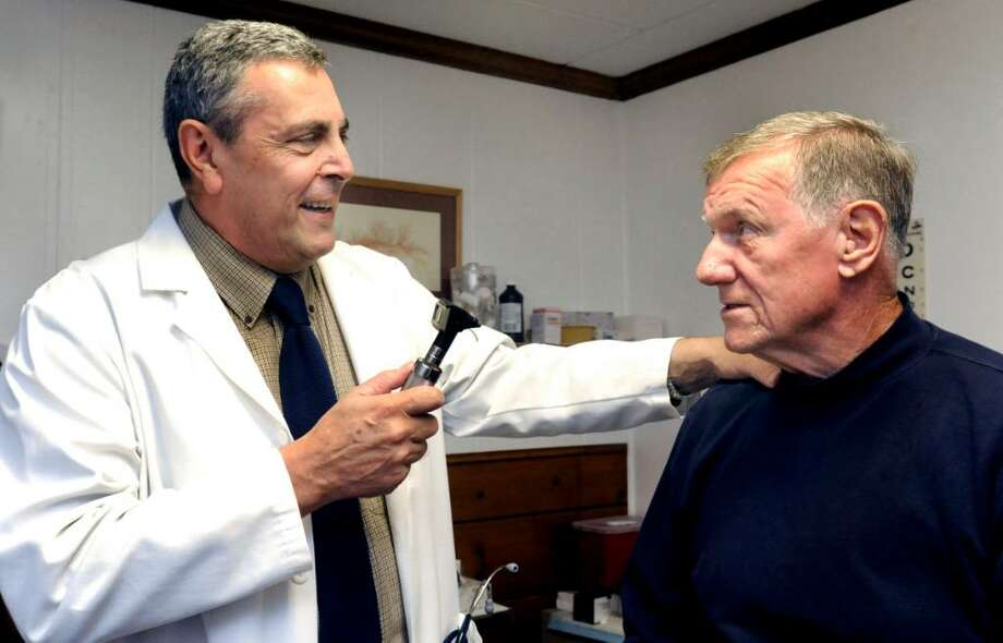 Dr. Edward Valpintesta, 65, examines Richard Mann, 75, in his Bethel office on Tuesday, Sept. 29,2009. Photo: Michael Duffy / The News-Times
