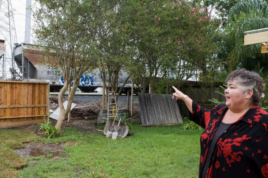 Judi Kissinger points to where a Union Pacific train derailed on July 2, knocking down fences and trees and causing damage to Kissinger's two rental properties in West University Place. Photo: R. Clayton McKee, For The Chronicle