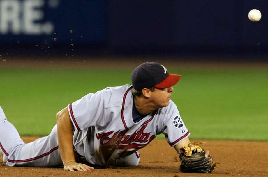 Braves second baseman Kelly Johnson fails to cleanly field a hard-hit grounder against the Mets. Photo: JIM McISAAC, GETTY IMAGES