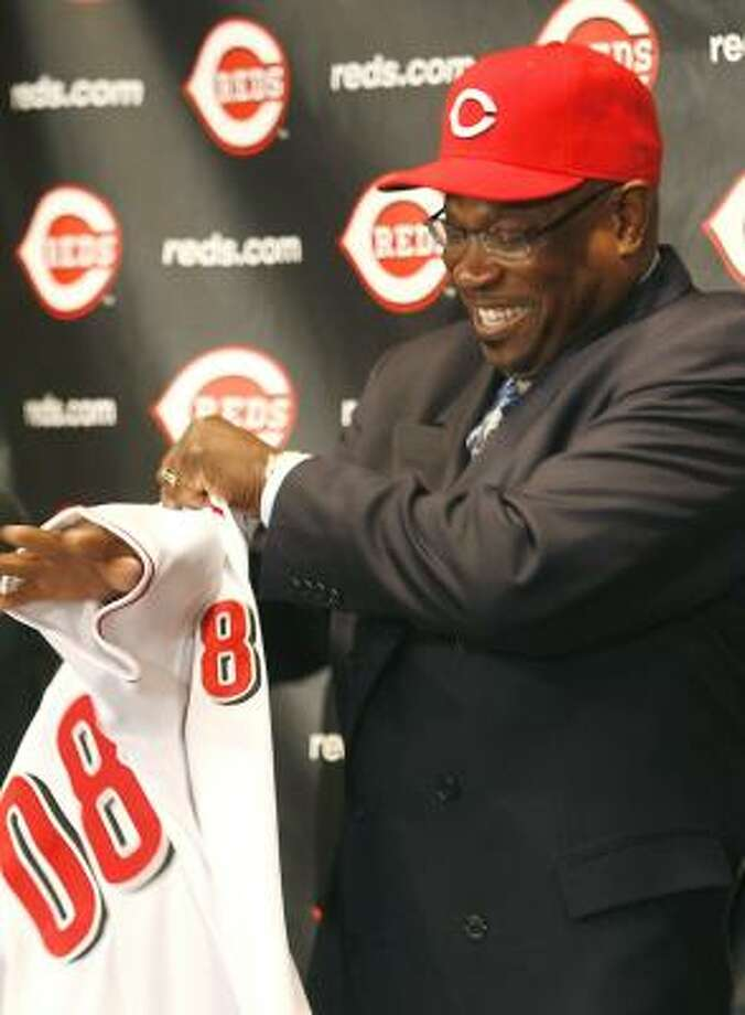 New Cincinnati Reds manager Dusty Baker puts on a Reds'  jersey after being introduced at Great American Ball Park Monday. Photo: David Kohl, AP