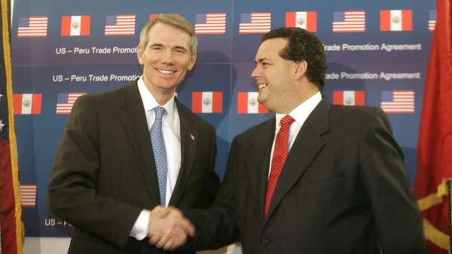 U.S. Trade Representative Rob Portman, left, and Peruvian Minister of Foreign Trade Alfredo Ferrero Diez Canseco mark the completion of free trade negotiations. Photo: LAWRENCE JACKSON, ASSOCIATED PRESS