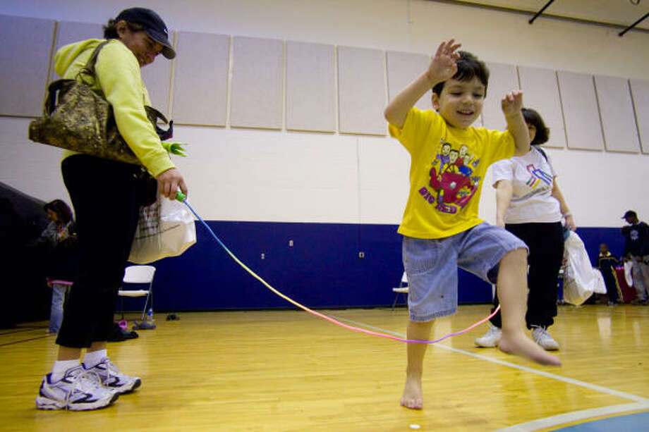 Matthew Kalmans, 4, gets his first jump rope lesson from mom Melissa Kalmans, left, and Shari Epstein, right, at the Jewish Community Center's Family Fun Day. Photo: R. Clayton McKee, For The Chronicle