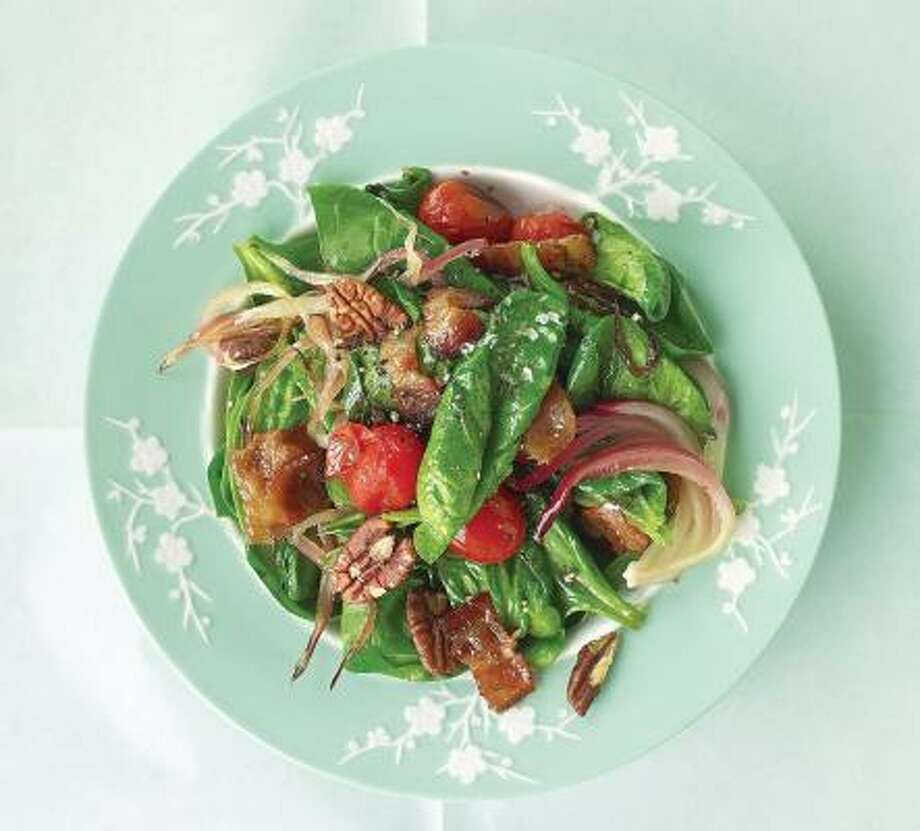 This recipe for Warm Spinach Salad With Bacon, Tomatoes and Pecans makes a colorful side dish or meal. Photo: DAVID LOFTUS, EVERYDAY FOOD
