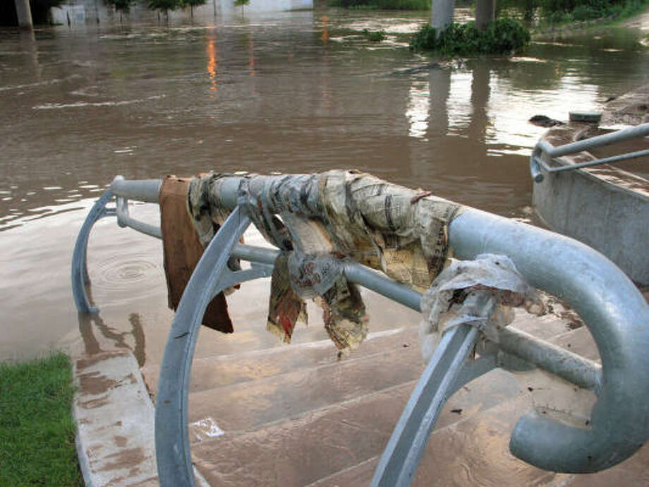 The swollen Buffalo Bayou left debris  on the handrail entrance to the bayou between Travis and Milam. Photo: The' N. Pham, CHRONICLE