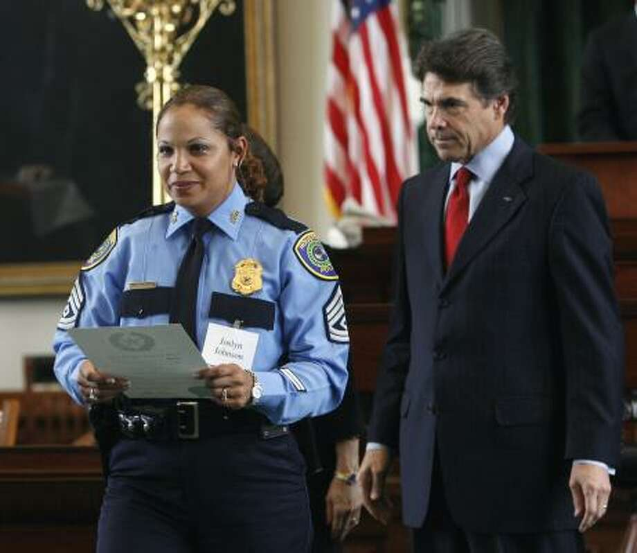 Houston police Sgt. Joslyn Johnson accepted a Star of Texas Award from Gov. Rick Perry on behalf of her husband, Officer Rodney Johnson, who was shot to death on Sept. 21, 2006. Photo: Harry Cabluck, Associated Press