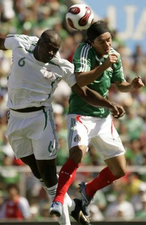 Nigeria's Danny Shittu battles Mexico's Juan Carlos Cacho during a 2-2 tie. Photo: GUILLERMO ARIAS, AP