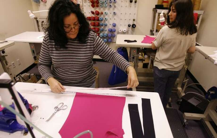 Noemy Puente, left, and Maria Muralles are staying busy at Fit Couture, a Houston-based online exercise wear company. Owners Amy and Mike Cerny say the weaker dollar is helping their bottom line. Photo: MELISSA PHILLIP, CHRONICLE