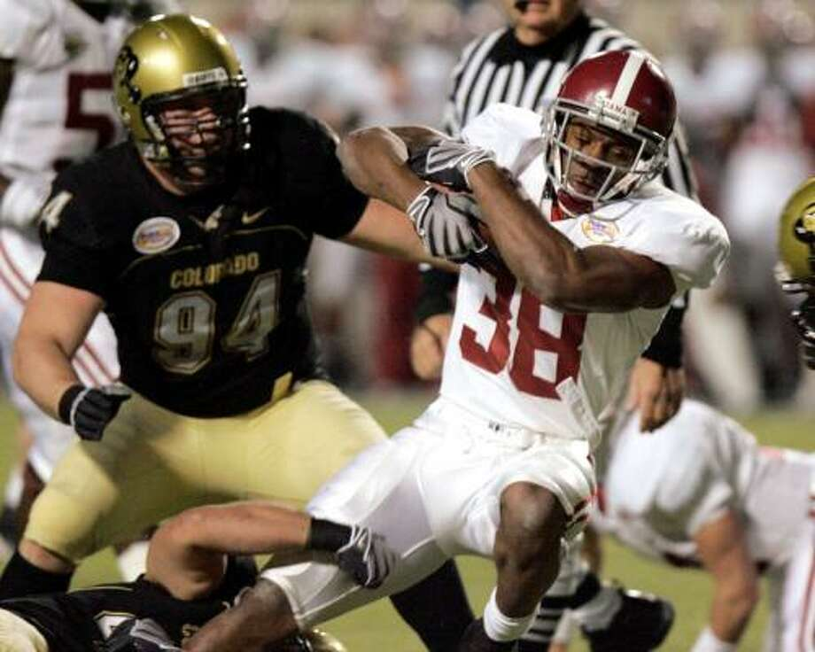 Alabama running back Glen Coffee, right, keeps his grip on the ball as Colorado's Brandon Nicolas goes for the tackle Sunday night in Shreveport, La. Photo: ROGELIO V. SOLIS, ASSOCIATED PRESS