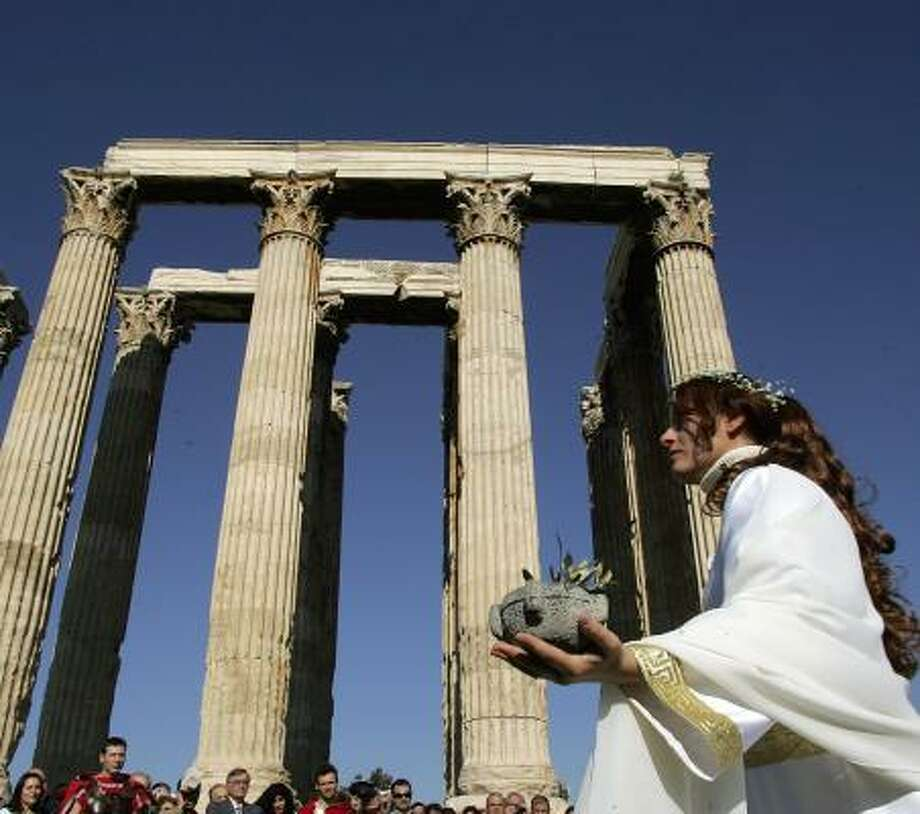 Pagans participate in a ceremony Sunday at a 1,800-year-old temple in Athens. Photo: LOUISA GOULIAMAKI, AFP/GETTY IMAGES