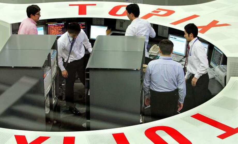 Traders on the Tokyo Stock Exchange confer during a recent session. In a sign of new economic openness, Japanese firms are now the hunters and the hunted. Photo: ITSUO INOUYE, ASSOCIATED PRESS