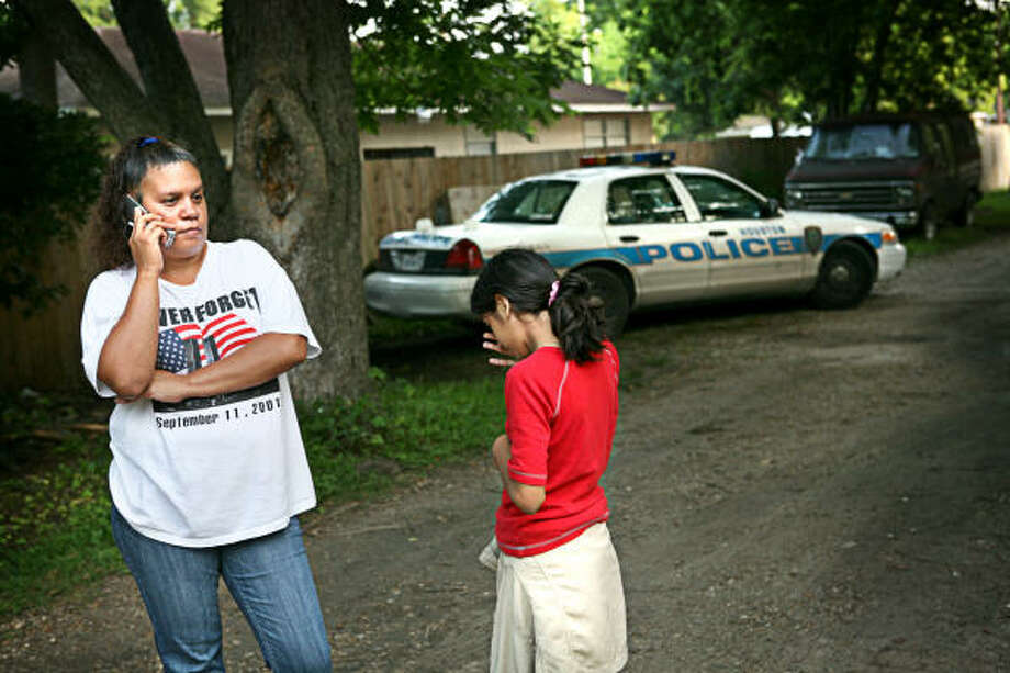 Rita Garcia stands with her daughter, 10, while police investigate in their neighborhood on Wednesday. Garcia, 37, said a man invaded her home around 2:30 a.m. Wednesday. Photo: ERIN TRIEB, FOR THE CHRONICLE