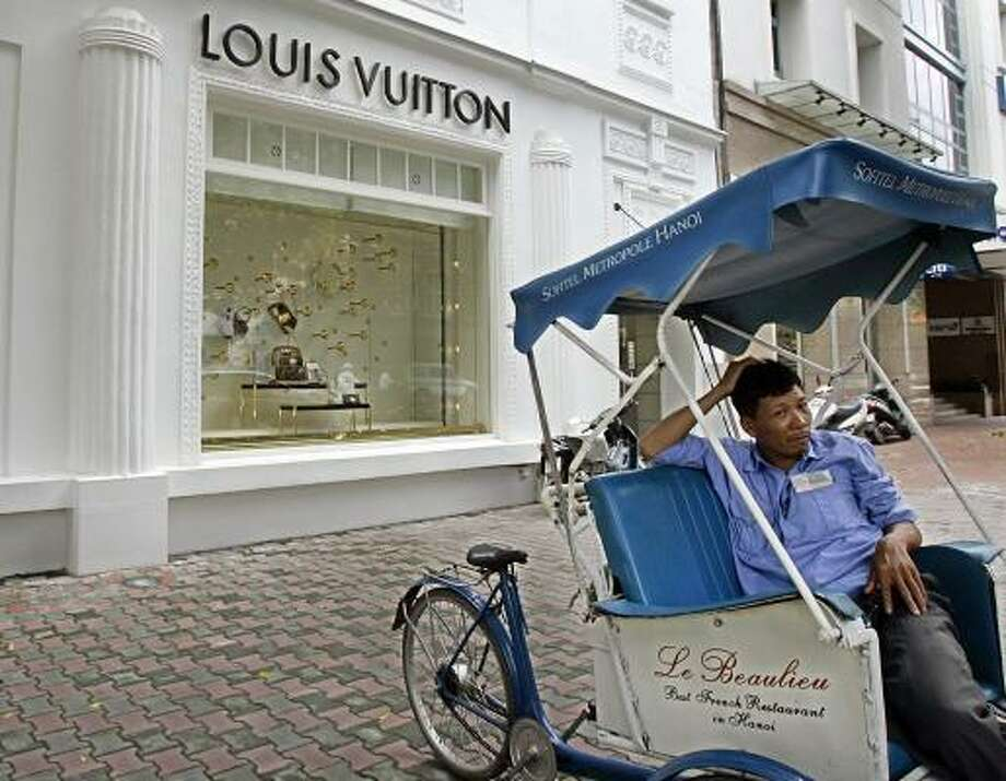 A pedicab driver waits for customers in front of a Louis Vuitton store in Hanoi, Vietnam, last month. The luxury market is booming in Vietnam, where Ho Chi Minh's communist revolution exalted equality and the common man in the mid-20th century. Photo: CHITOSE SUZUKI, ASSOCIATED PRESS