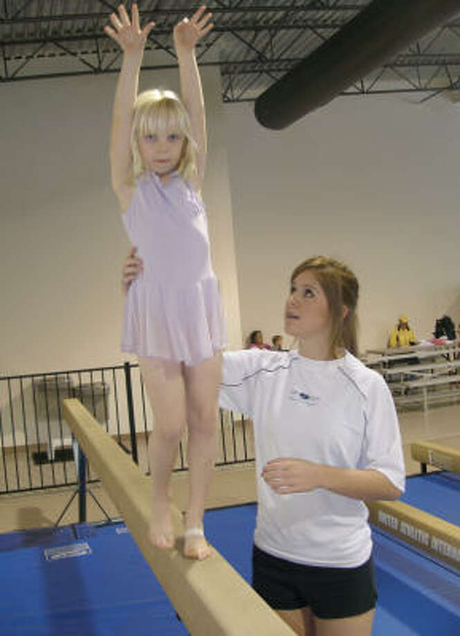 Jessica Bills, one of the coaches at Juergen's Gymnastics Academy at Orleans Square Shopping Center on W. Lake Houston Parkway, helps a pupil on the balance beam. Photo: HARRY WILLIAMSON, FOR THE CHRONICLE