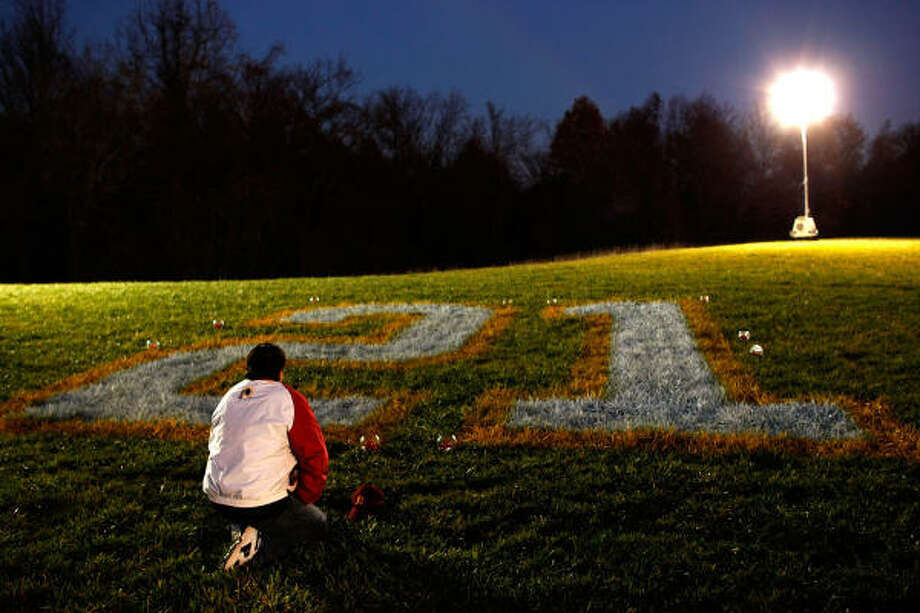 Redskins fan Timothy McLeod kneels before Sean Taylor's No. 21 at a makeshift memorial for the slain football player Tuesday at Redskins Park. Photo: Win McNamee, Getty Images