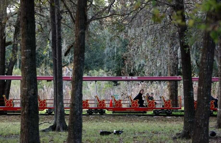 Alida Olson, son Anders, 2, and daughter Olivia, 4, ride Monday on Hermann Park's train, which makes its last stop Jan. 1. A new version opening in March will service museums and link to light rail. Photo: JOHNNY HANSON, CHRONICLE