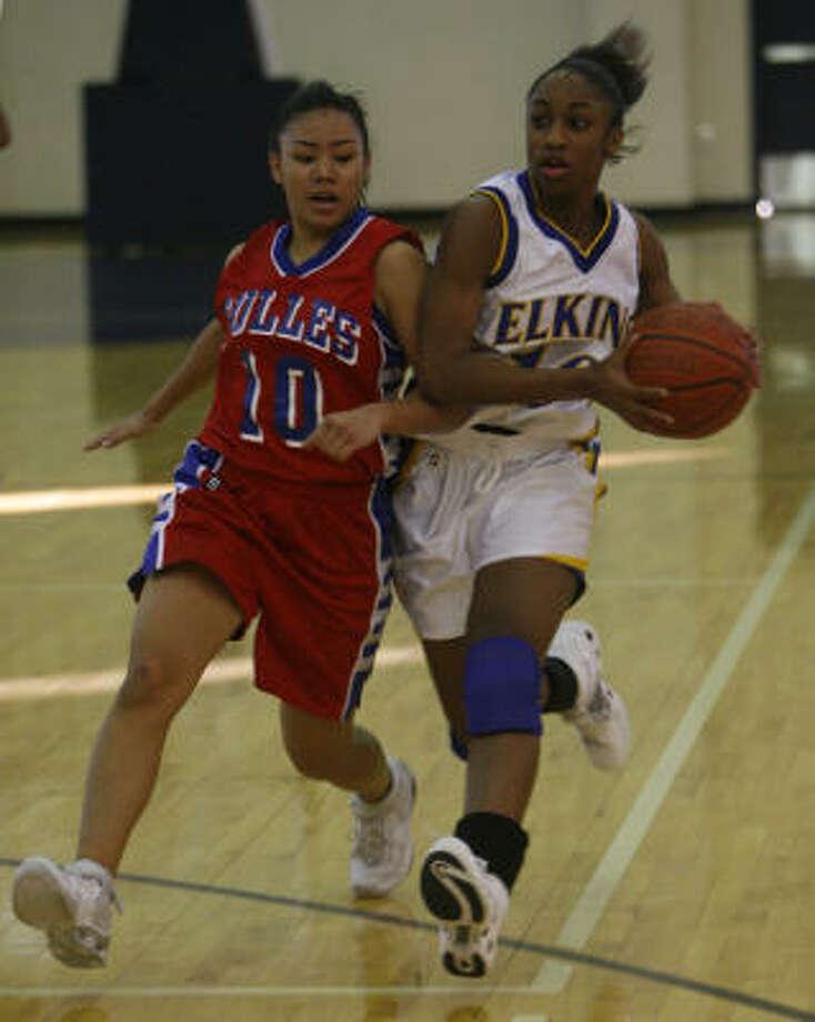 Elkins' Skylar Hunt drives against Dulles' Priscilla Galliguez. Photo: Carlos Antonio Rios, Chronicle