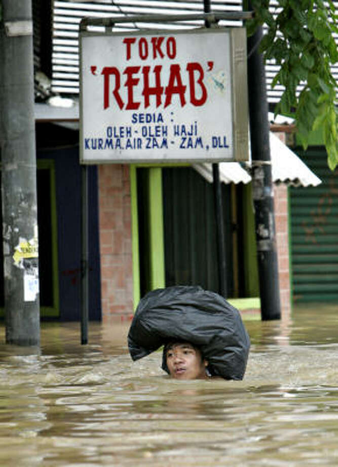 An Indonesian man wades through a flooded street after heavy rains overwhelmed much of Jakarta, Indonesia, on Monday. Waterborne disease is the next worry, officials say. Photo: ED WRAY, AP