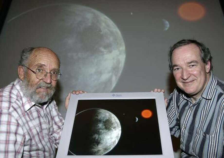 Swiss astrophysicist and director of the Geneva Observatory, Michel Mayor, left, and Swiss astrophysicist Stephane Udry, right, hold an artist rendering on Tuesday showing the planetary system around the red dwarf Gliese 581. Mayor and Udry have discovered a planet outside our solar system that is potentially as habitable as Earth, at left, with similar temperatures, they announced. Photo: SALVATORE DI NOLFI, AP