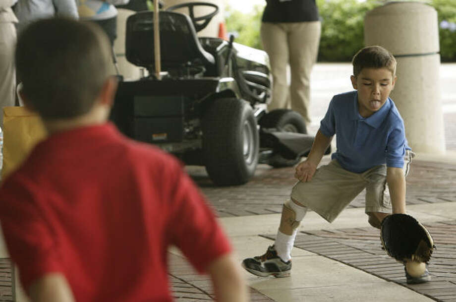 Alex Macejewski, 8, left, and brother Eddie Macejewski, 7, practice throwing a baseball after an event at Shriners Hospital for Children on Tuesday promoting lawn mower safety. Eddie was accidentally run over by a lawn mower driven by his father four years ago, but with the help of a prosthetic foot now plays on a baseball team. Photo: Mayra Beltran, Chronicle