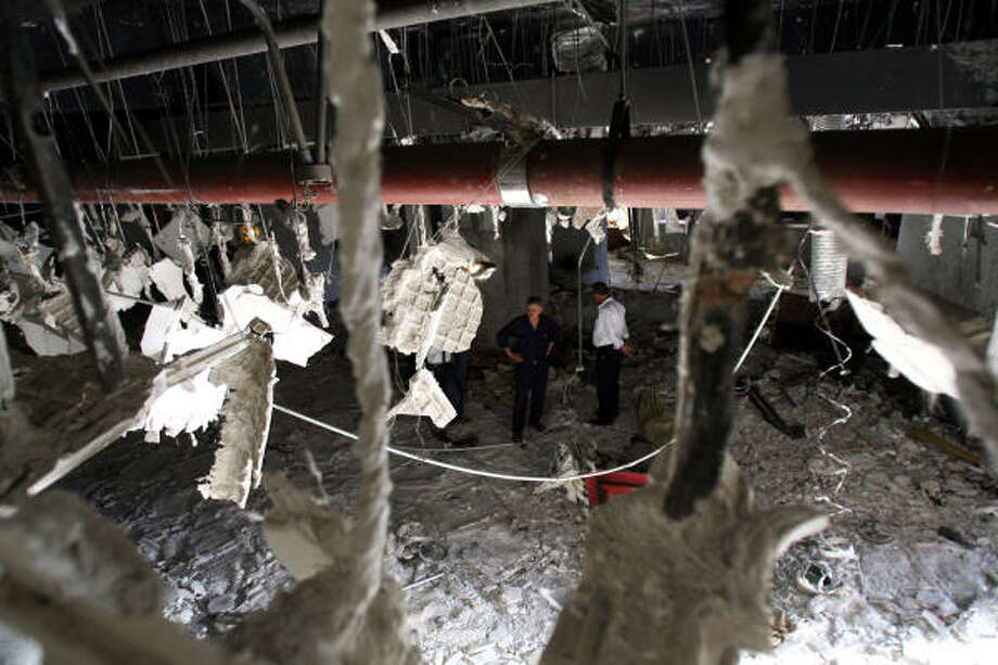 People inspect the bombed-out lobby of the Mansour Hotel in Baghdad on Monday. A suicide bomber, apparently targeting a meeting of U.S.-allied Sunni sheiks, penetrated layers of security and blew himself up in the lobby, killing four of the tribal leaders and at least eight other people, police reported. Photo: HADI MIZBAN, AP