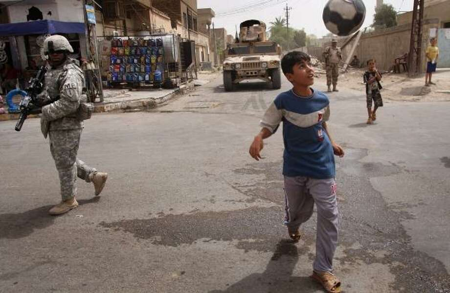 An Iraqi boy appears oblivious to U.S. troops as he plays with a soccer ball while walking on a street in the Hurriyah neighborhood of Baghdad on Saturday. Violence is down in the Shiite area since Muqtada al-Sadr announced that he was halting offensive operations. Photo: JOHN MOORE, GETTY IMAGES