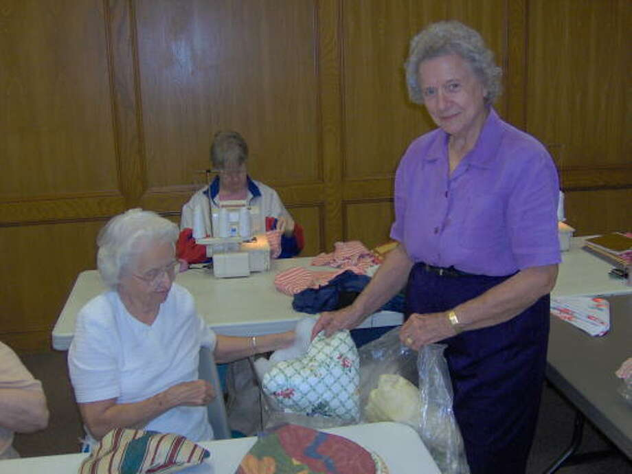 Pedal Pusher founder Bernice Wallace, right, helps Ruby Smith ready a delivery of heart pillows for breast cancer patients. In the background, Mary Lyn Bramblett works on other items  for donation. Photo: Stephanie King, For The Chronicle