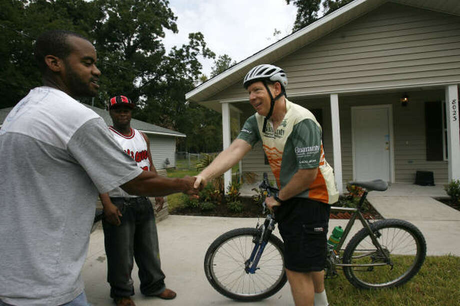 Mayor Bill White meets Bernard Price, a new owner of a Habitat for Humanity house on Dockal Road in northeast Houston. White and other offiicials took a bike tour Sunday as part of the Hope program, through which the city buys abandoned properties and turns them into affordable housing. At center is fellow home owner and evacuee Corey French. Photo: Sharon Steinmann, Chronicle