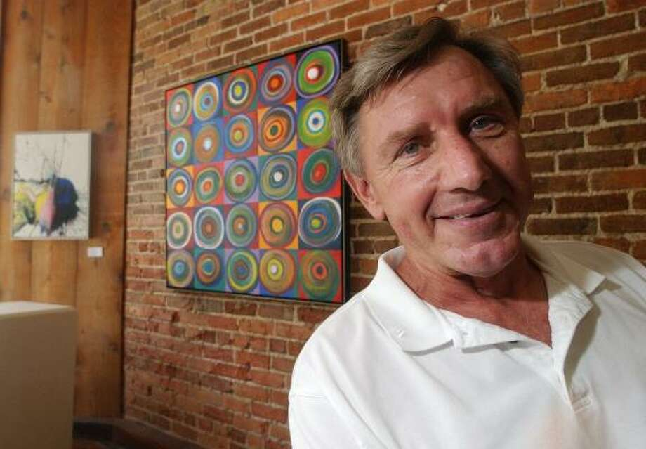 Four-time Olympic gold medalist Al Oerter stands in front of some of his artwork, much of which was created by smashing a discus into puddles of paint on canvas. Photo: TERRY ALLEN WILLIAMS, ASSOCIATED PRESS